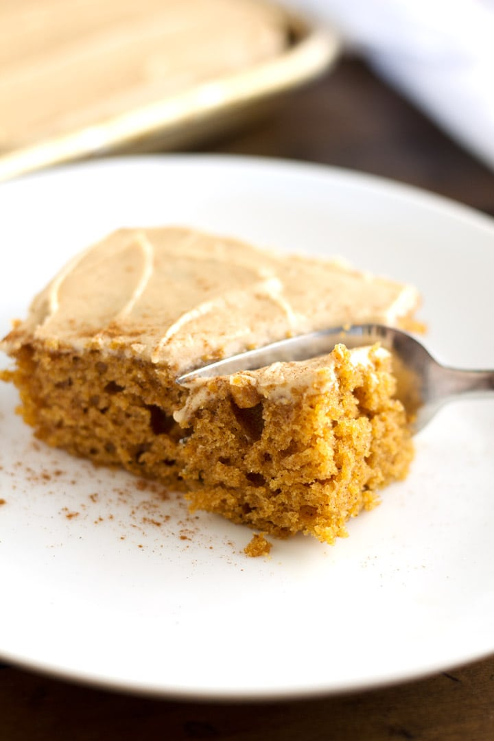Piece of pumpkin sheet cake on plate with whole cake in background.