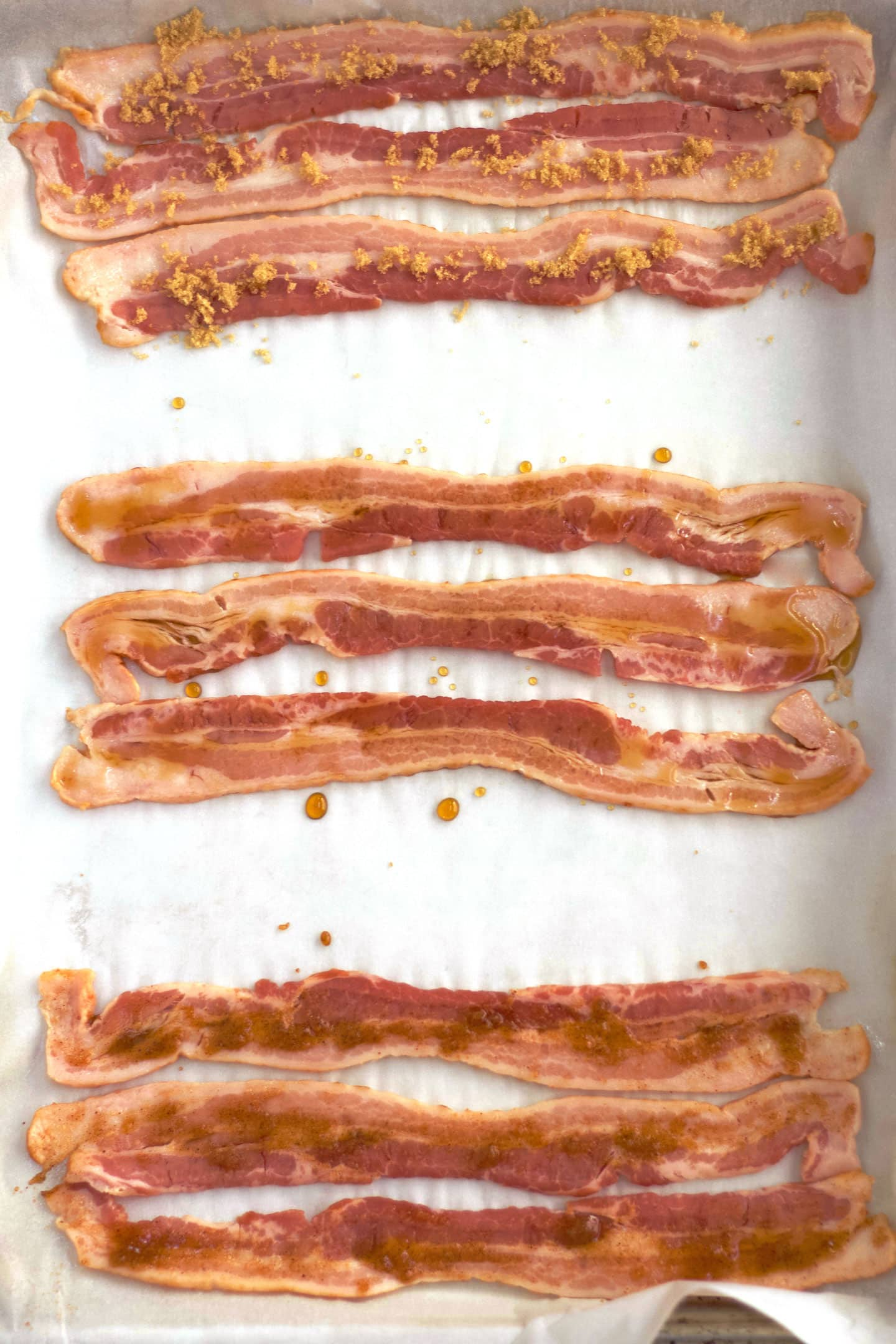 Raw bacon on sheet pan with toppings.