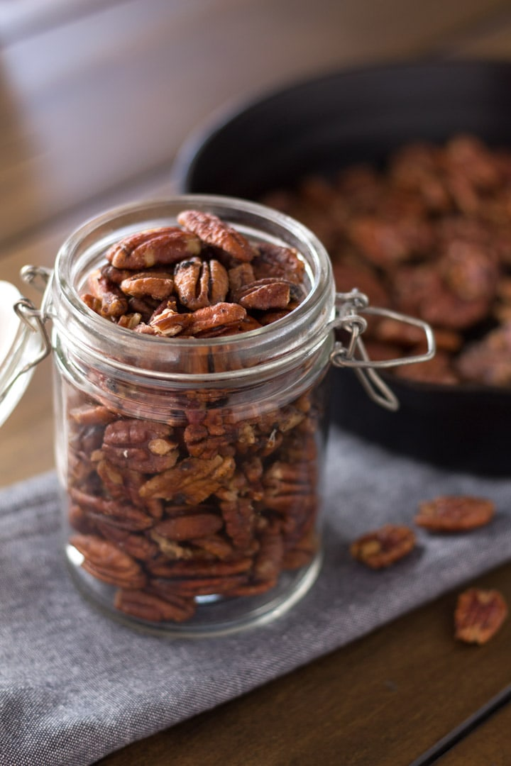 Mapled pecans in jar with pan in background