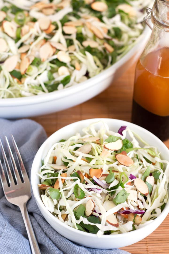 Bowl of Easy Asian Slaw Salad with fork and larger serving bowl in background