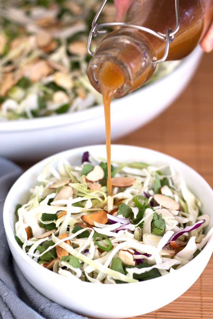 Pouring dressing on asian slaw salad