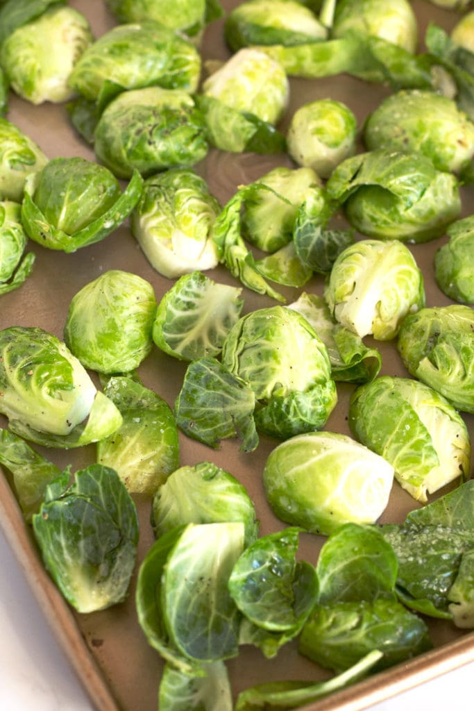 Corner of sheet pan with raw brussels sprouts.