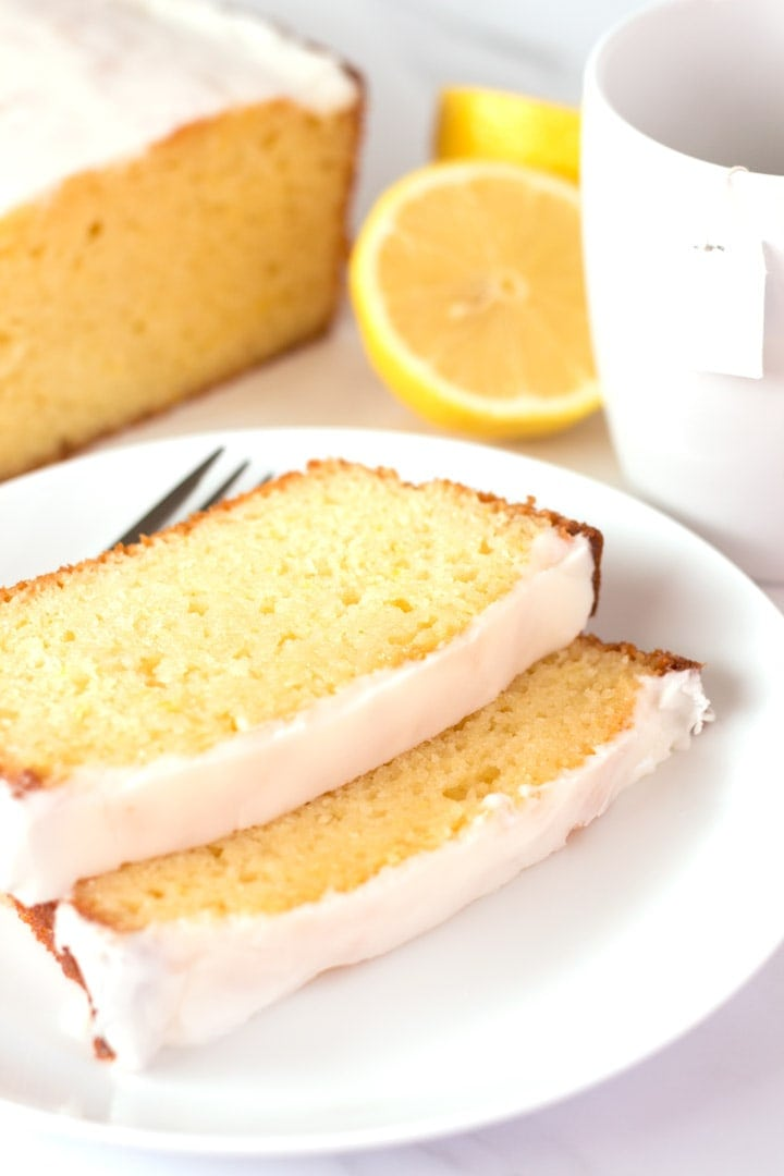 Two slices of lemon yogurt cake with tea cup and full cake in background.