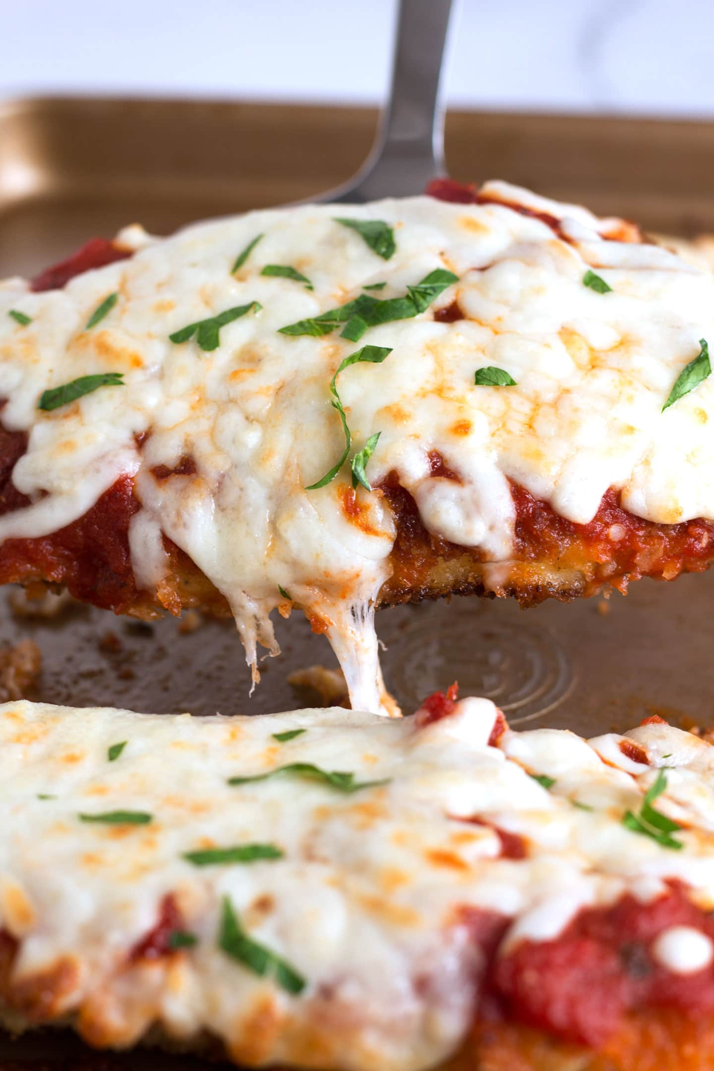 Spatula lifting gooey and crispy Chicken Parmesan
