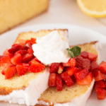 Lemon Yogurt Cake with strawberries on top with text overlay.