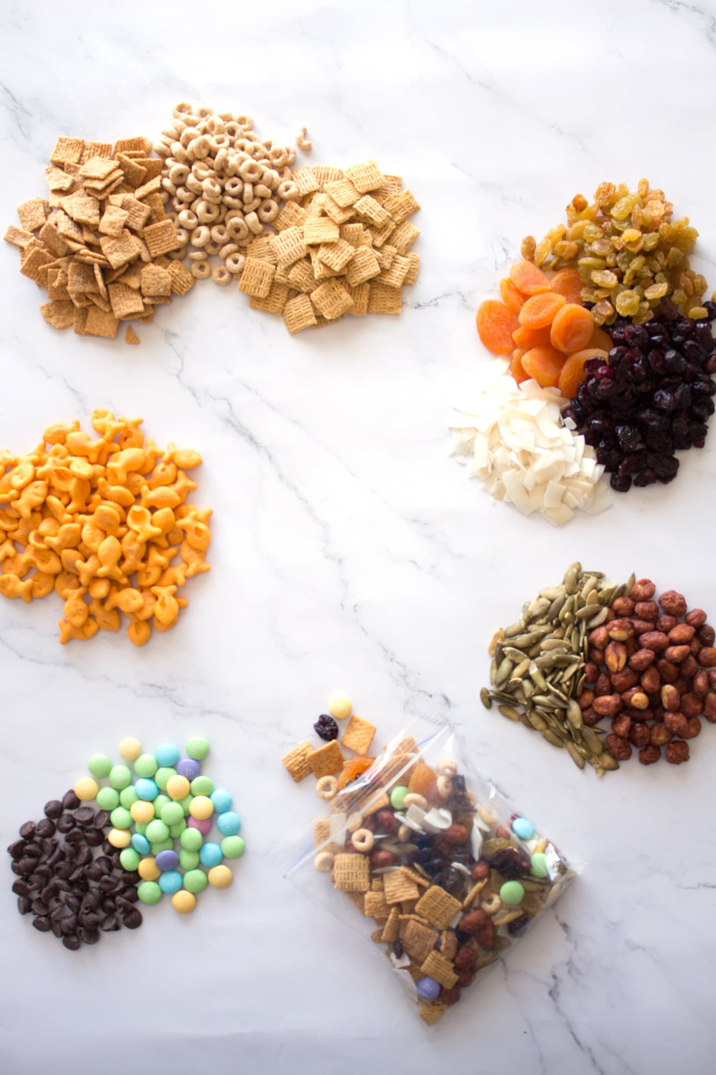 Different trail mix elements in piles on counter