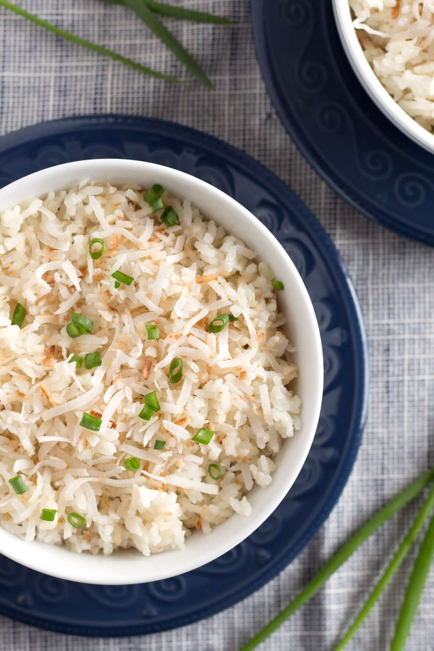 Overhead of bowls of Instant Pot Toasted Coconut Rice on blue plates
