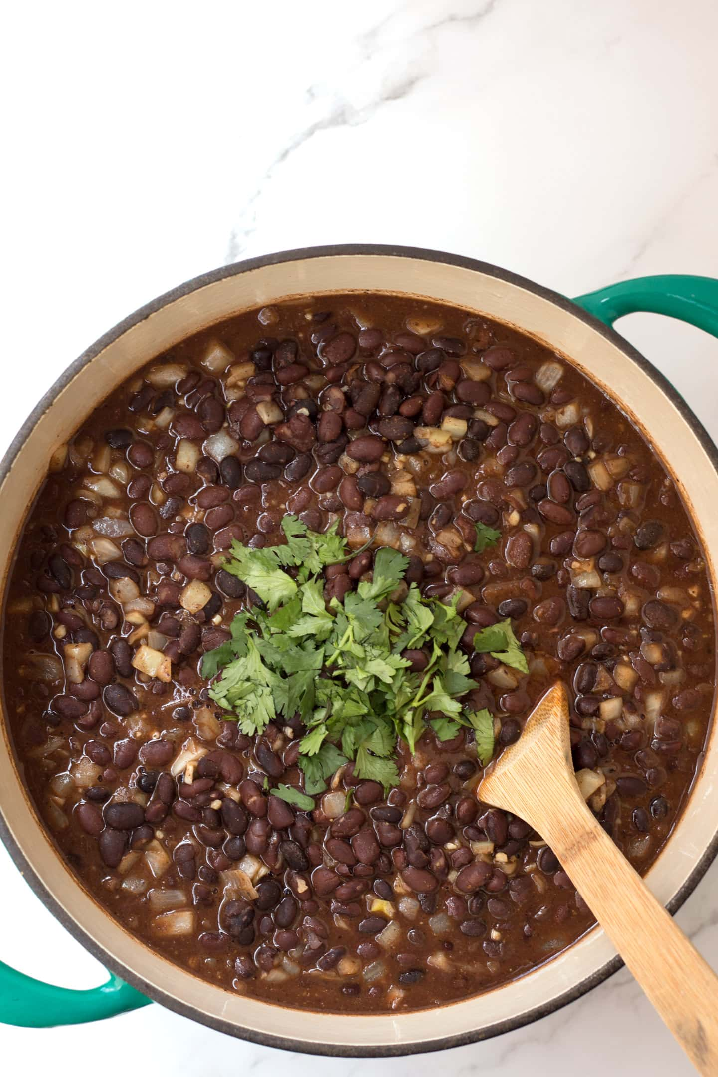 Pot of black beans with cilantro garnish.