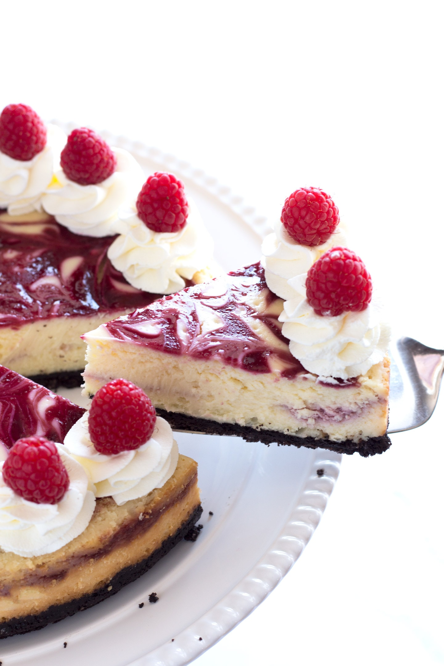 Removing slice of white chocolate raspberry cheesecake from white plate
