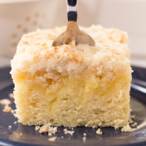 Lemon coffee cake with layer of lemon curd and crumb topping on a blue plate with fork in the middle.