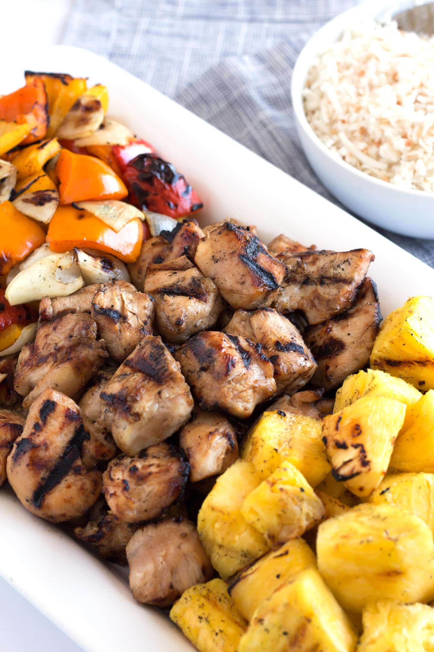 White platter with grilled honey chicken, vegetables, and pineapple.