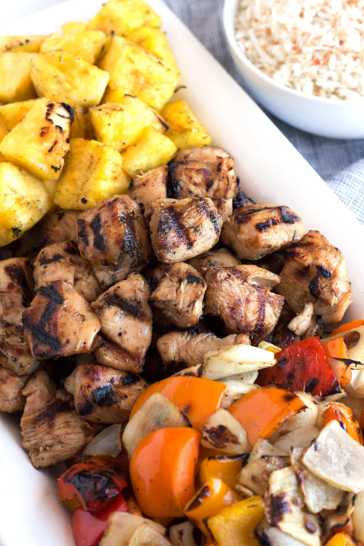 Grilled Honey Chicken Kabobs on a platter with rice in background.