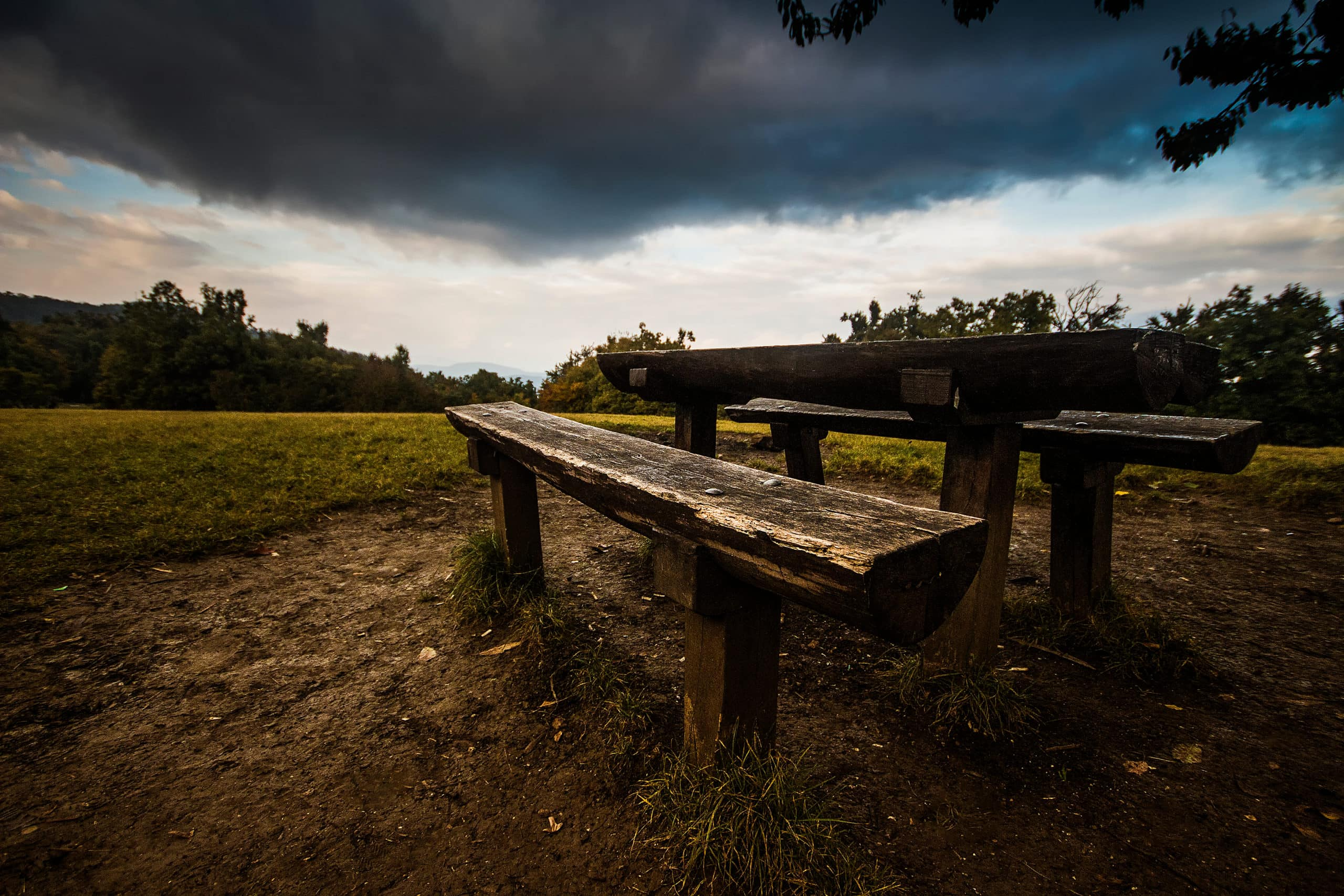 Rustic picnic table with meadow in background.