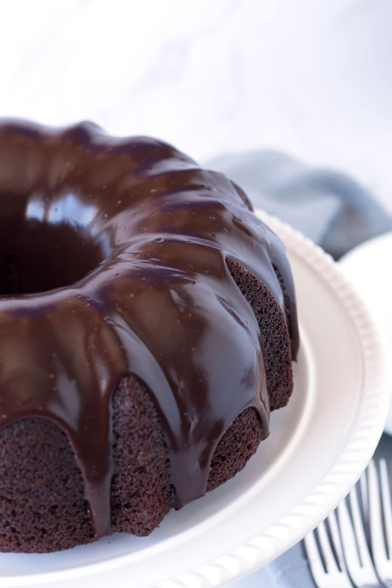 The perfect chocolate bundt cake on a cake plate with plates and forks