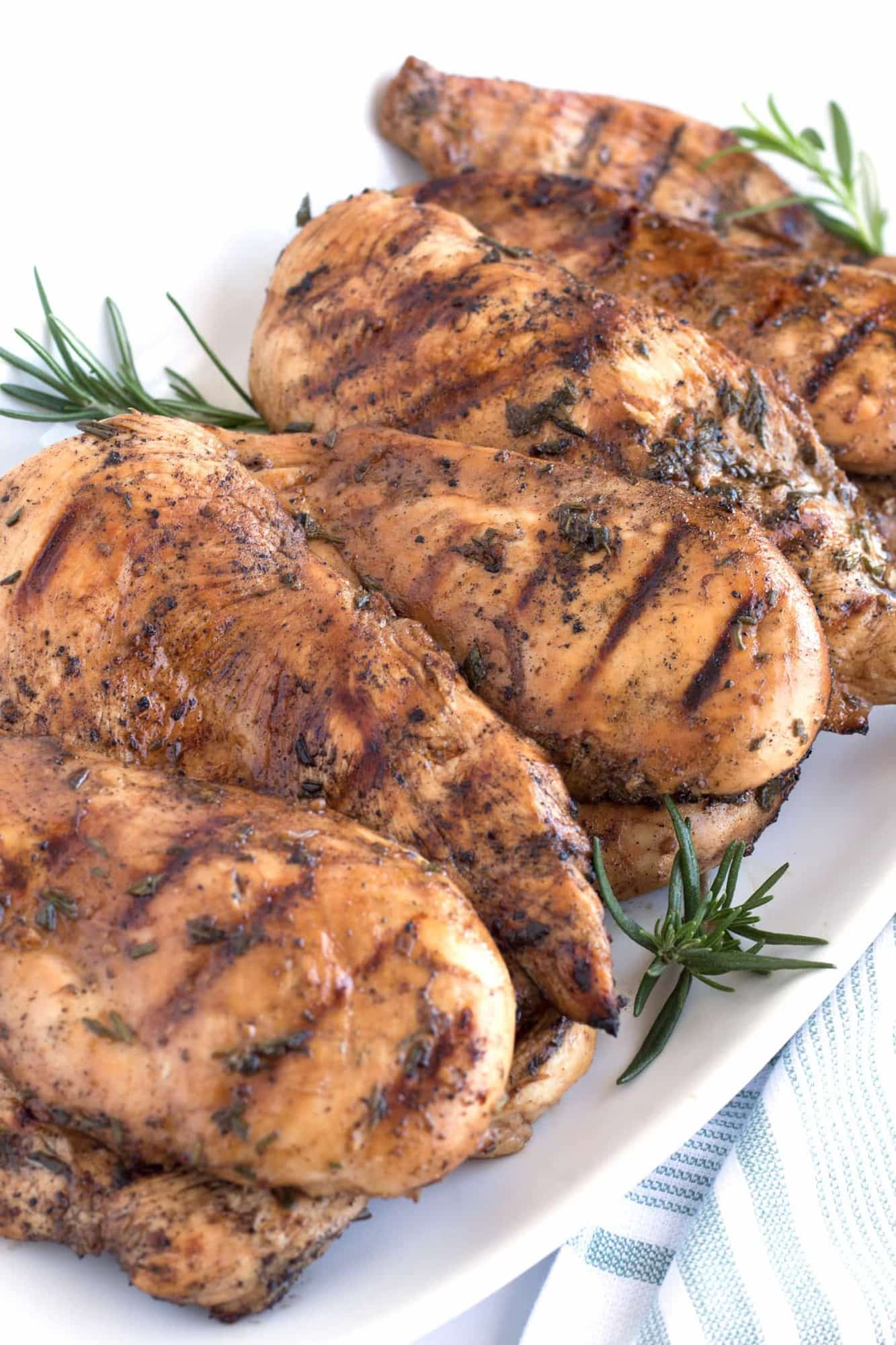 Full platter of grilled chicken with rosemary sprigs.