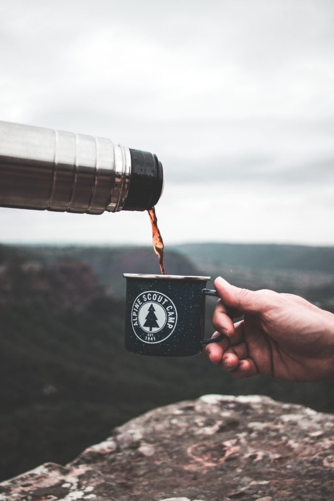 Coffee being poured into a cup with mountains in background.