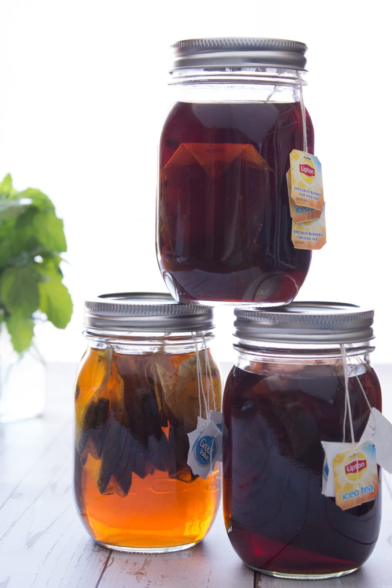Three jars of tea concentrate stacked off center with herbs in background.