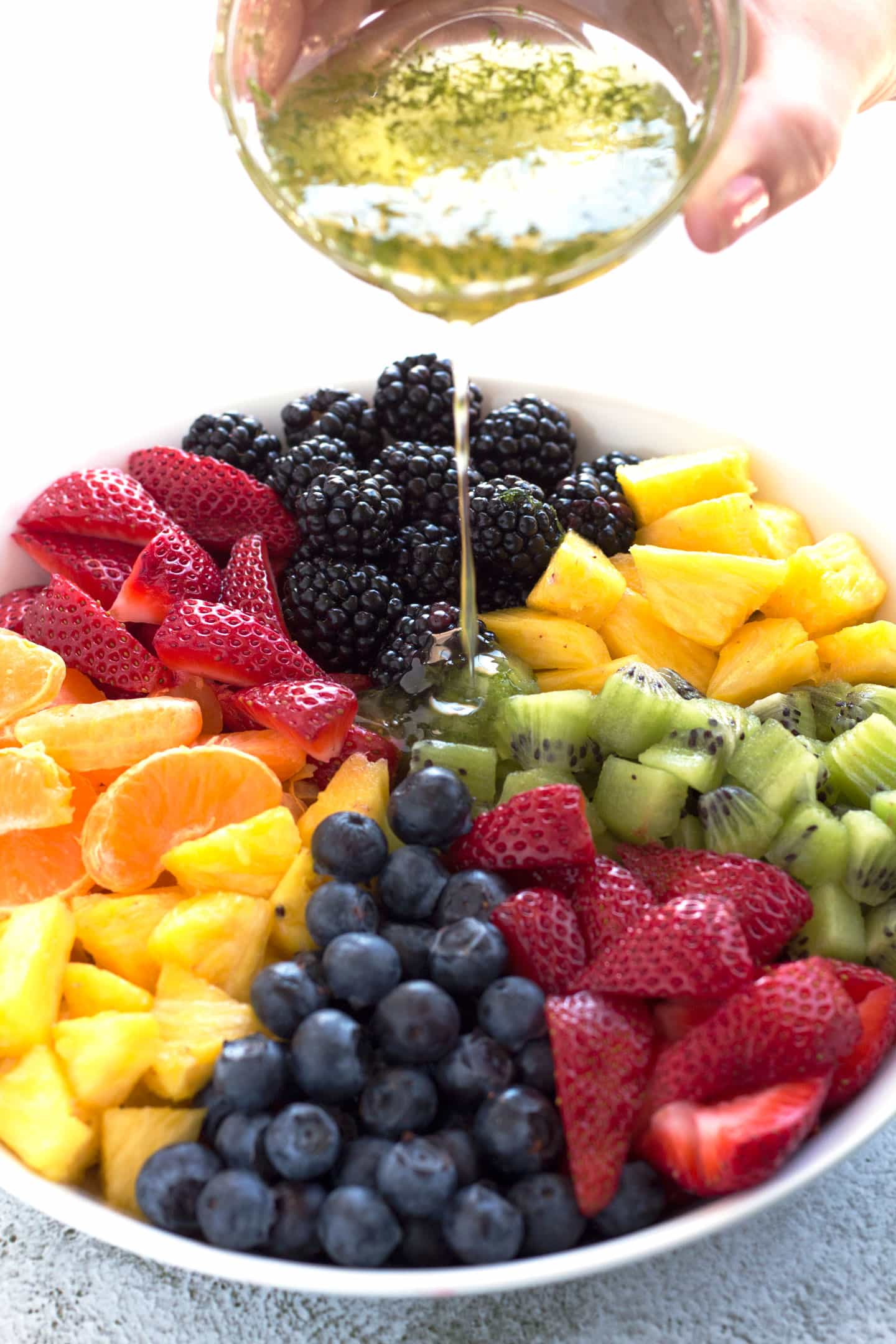 Pouring honey lime dressing on bowl of fruit salad