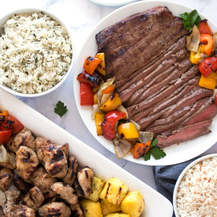 Grilled chicken, steak, and veggies with rice on platter.