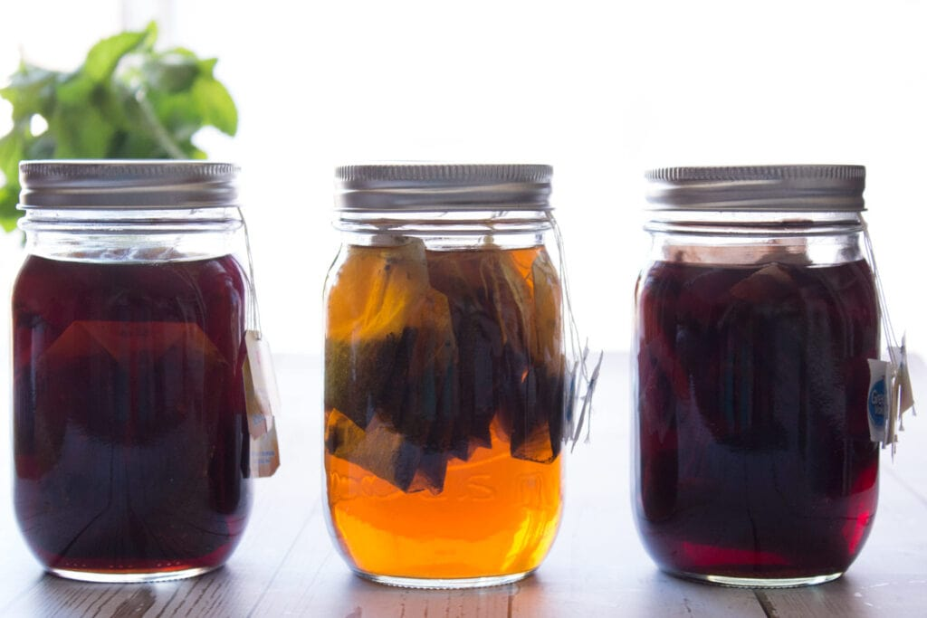 Three jars of black tea, fruit tea, and green tea concentrate lined up.