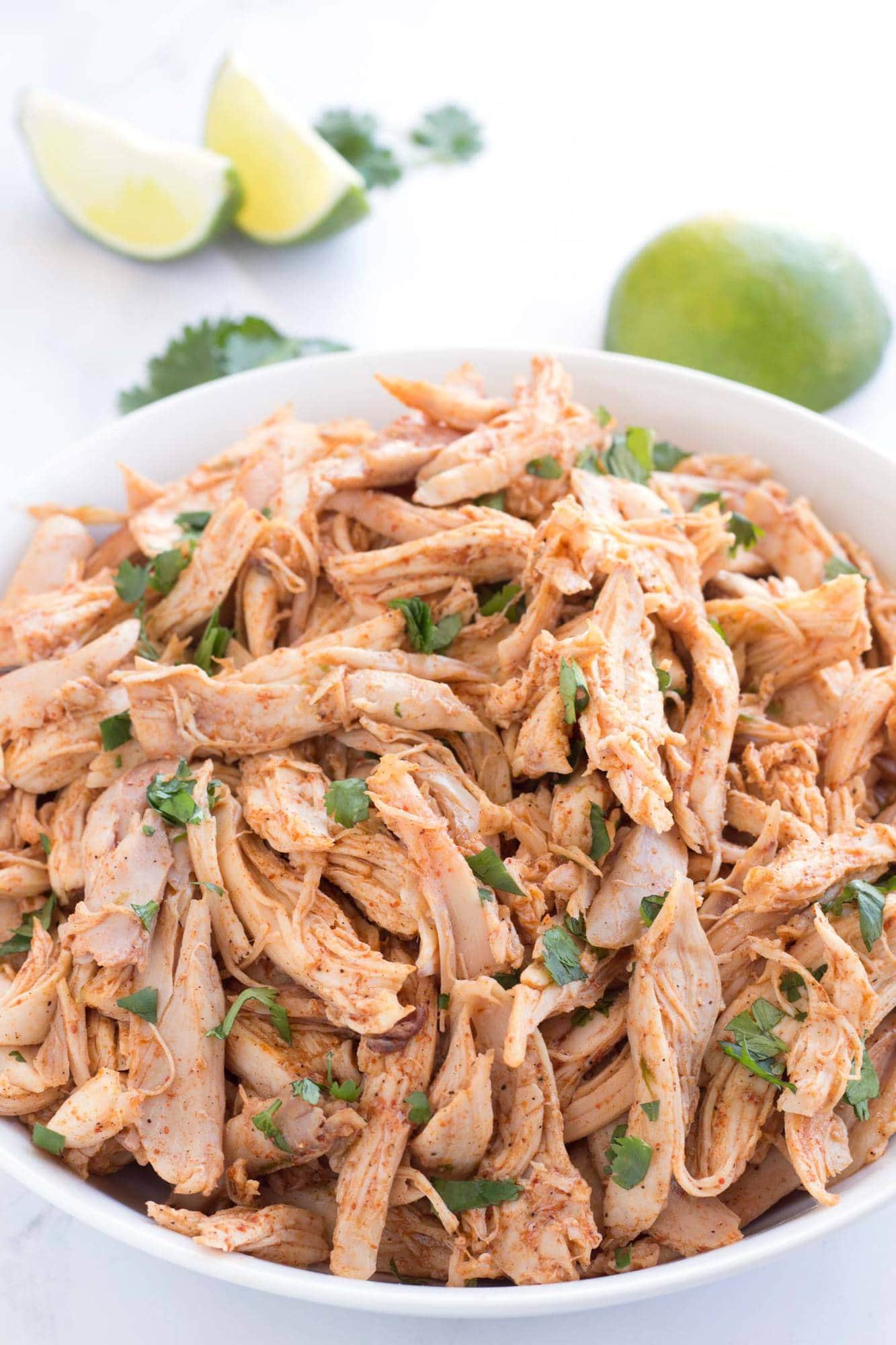 Full bowl of shredded chicken with cilantro sprinkled on top