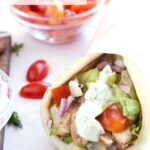 Grilled Greek Chicken Gyro drizzled with tzatziki sauce with graphic overlay