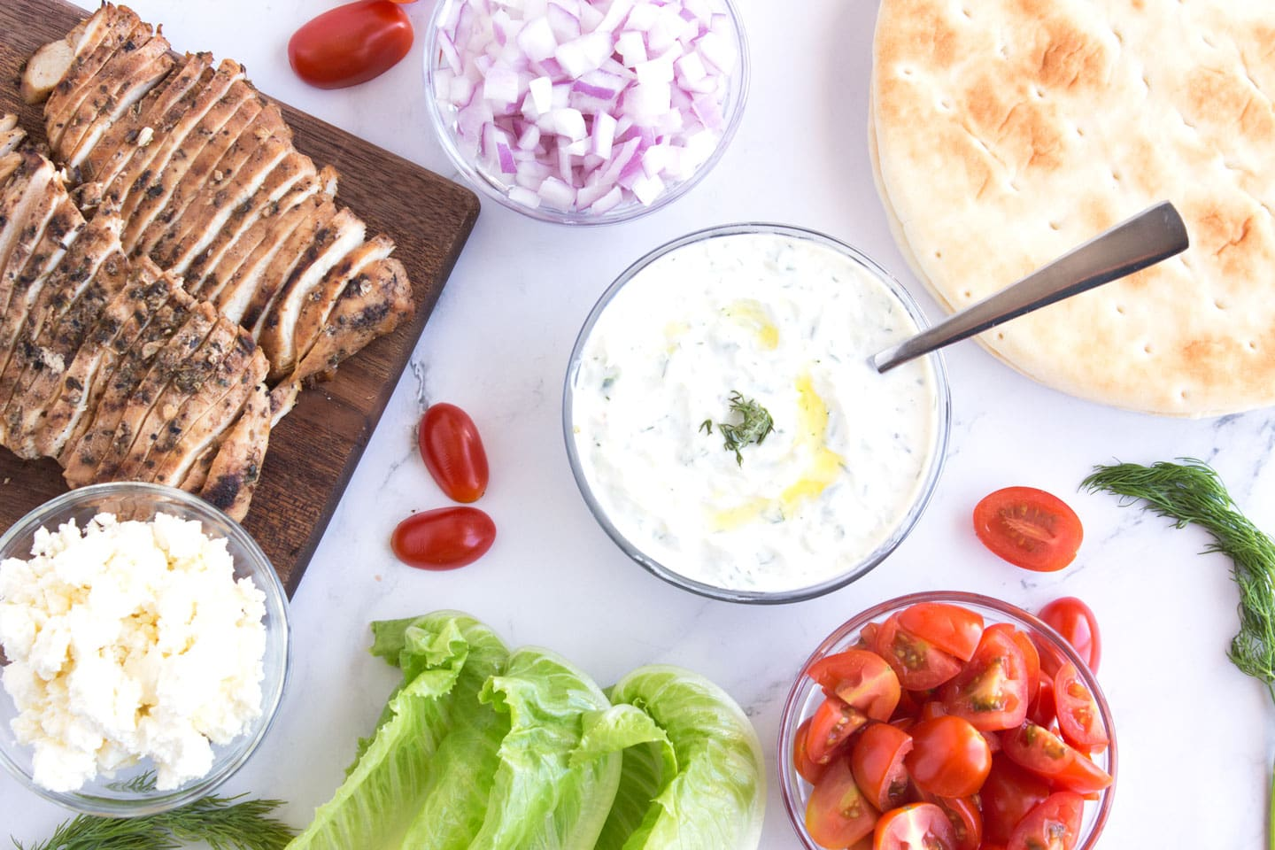 Ingredients for Grilled Greek Chicken Gyros on a countertop.