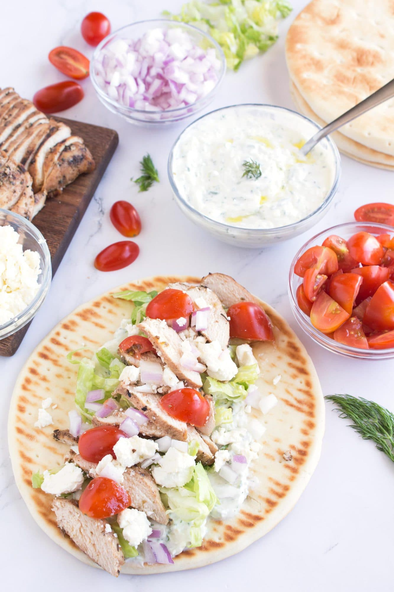 Pita layered with all the ingredients for a grilled chicken gyro.