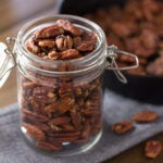 Open jar of maple pecans with cast iron pan in background