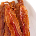 Strips of candied bacon on a platter.