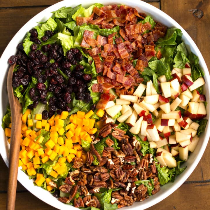 Pecans, cheese, cranberries, pears, bacon and lettuce in a bowl