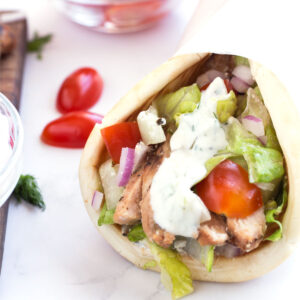 Pita bread around grilled chicken and drizzled with tzatziki sauce.