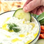 Cucumber dipping in tzatziki sauce with graphic overlay
