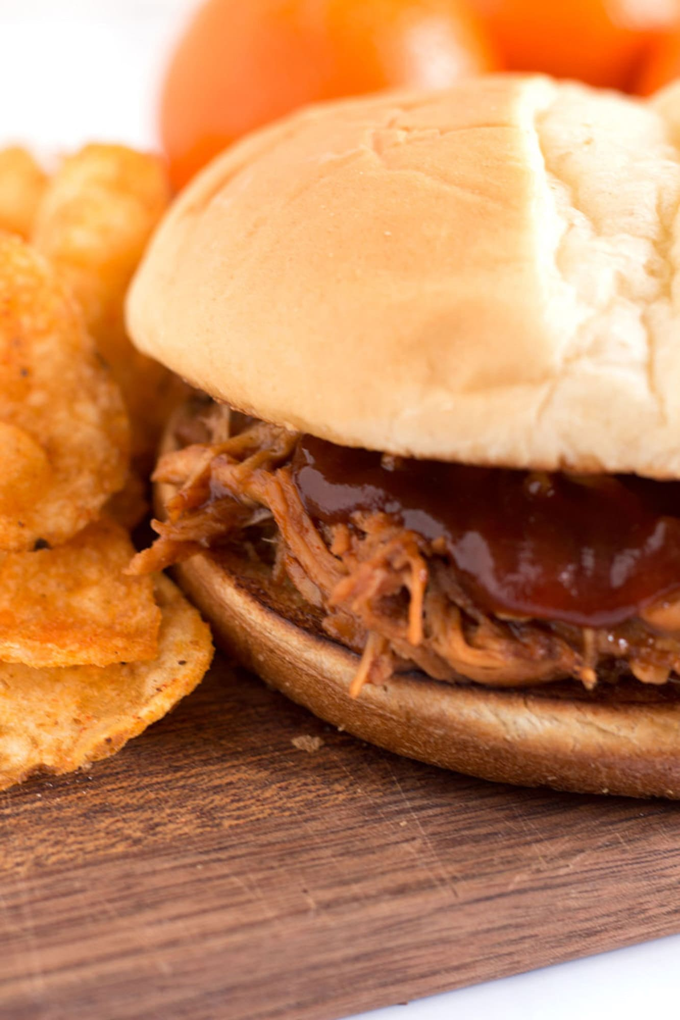Shredded BBQ chicken on a bun with chips and tangerines.