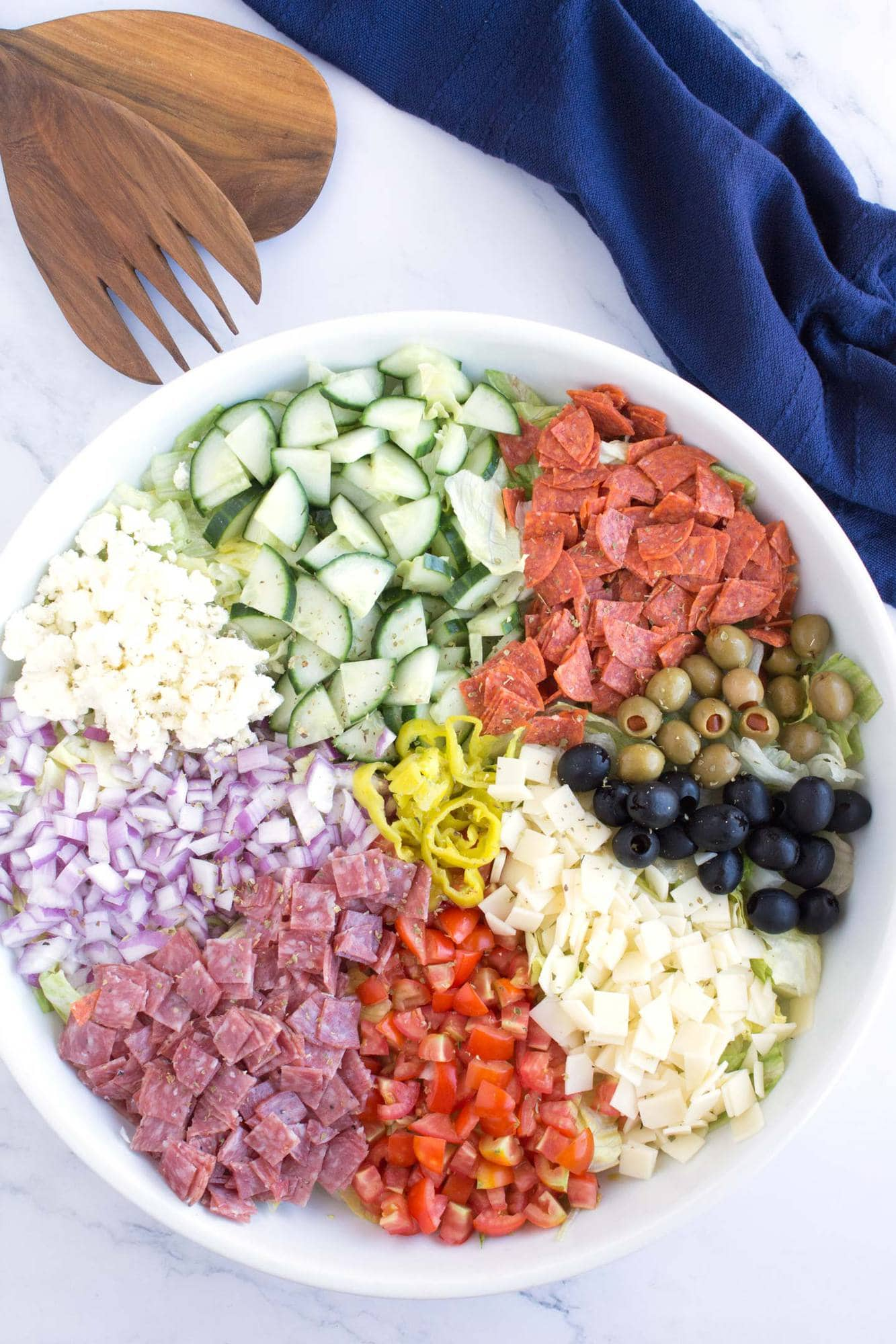 Italian Chopped Salad in serving bowl with blue towel and serving tongs.
