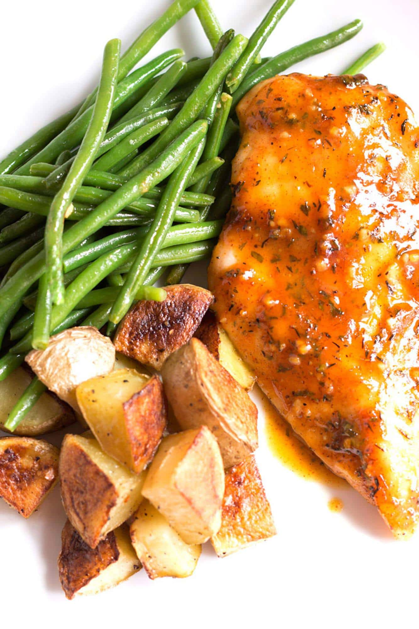 Honey mustard chicken, roasted potatoes, and green beans on a plate.