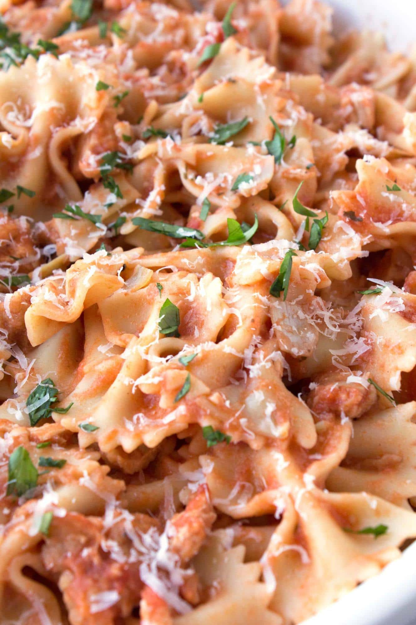 Close up of bowl of Easy Chicken Piccata Pasta with parmesan cheese and parsley on top