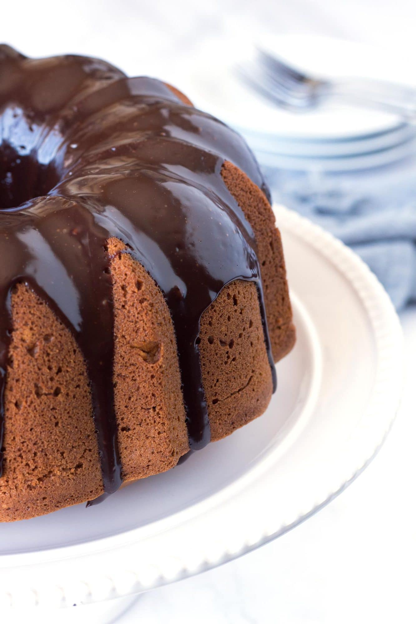 Side of Pumpkin Bundt Cake with Chocolate Ganache on white cake plate