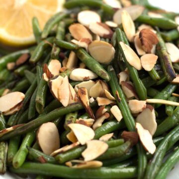 Green beans almondine with almonds and a lemon on a platter
