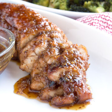 Pork tenderloin on serving platter with maple sauce
