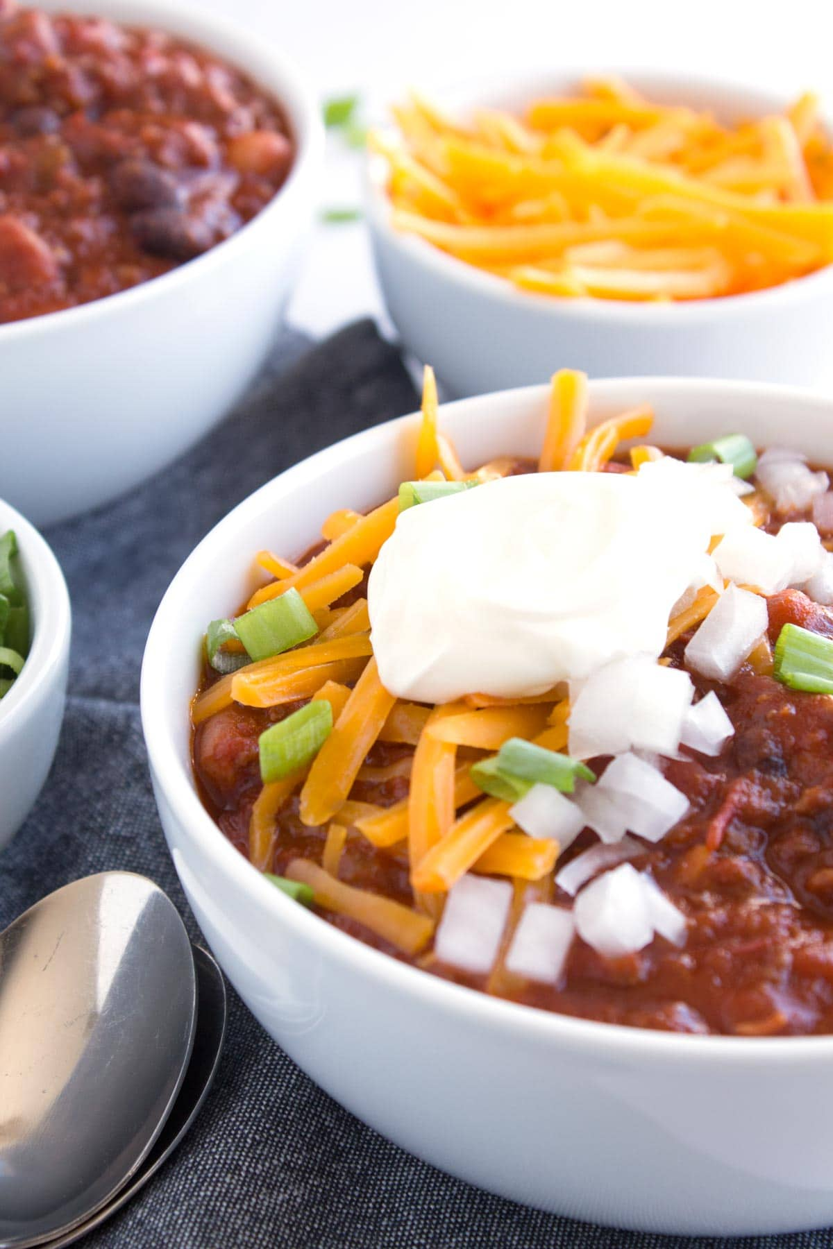 Two bowls of Best Easy Chili Recipe with toppings on counter.