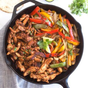 Overhead of cast iron skillet with chicken fajitas and blue towel.