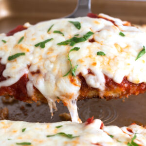 Crispy piece of Chicken Parmesan with melty cheese on top.