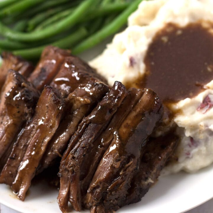 Green beans, mashed potatoes, and pot roast on a plate.
