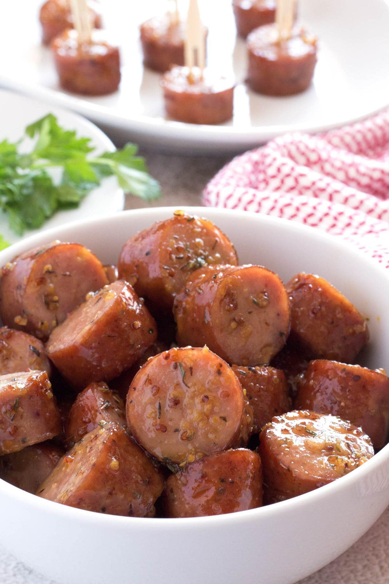 Pile of sausage bites in a bowl covered in maple glaze.