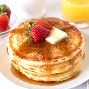 Panckaes on a white plate with strawberries and syrup.