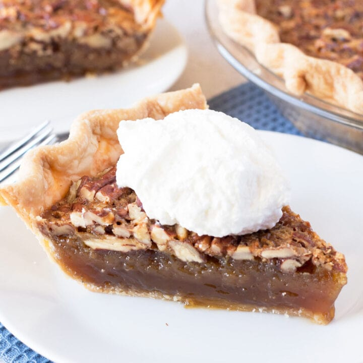 Slice of Pecan Pie on white plate with blue towel underneath