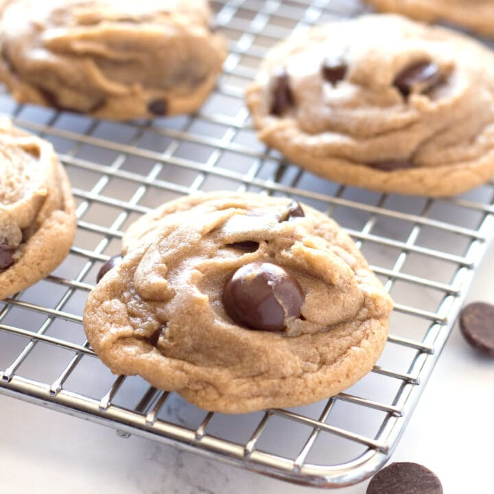 Chocolate chip cookie on cooling rack with more cookies in background