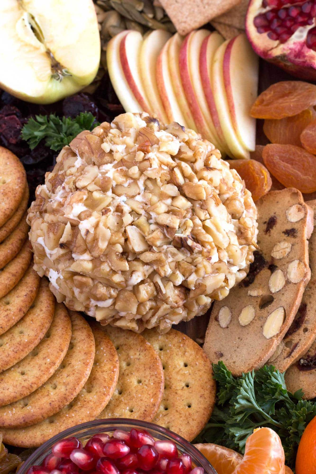 Cheese ball with ranch seasoning covered in walnuts and sitting on cutting board with crackers and fruit.