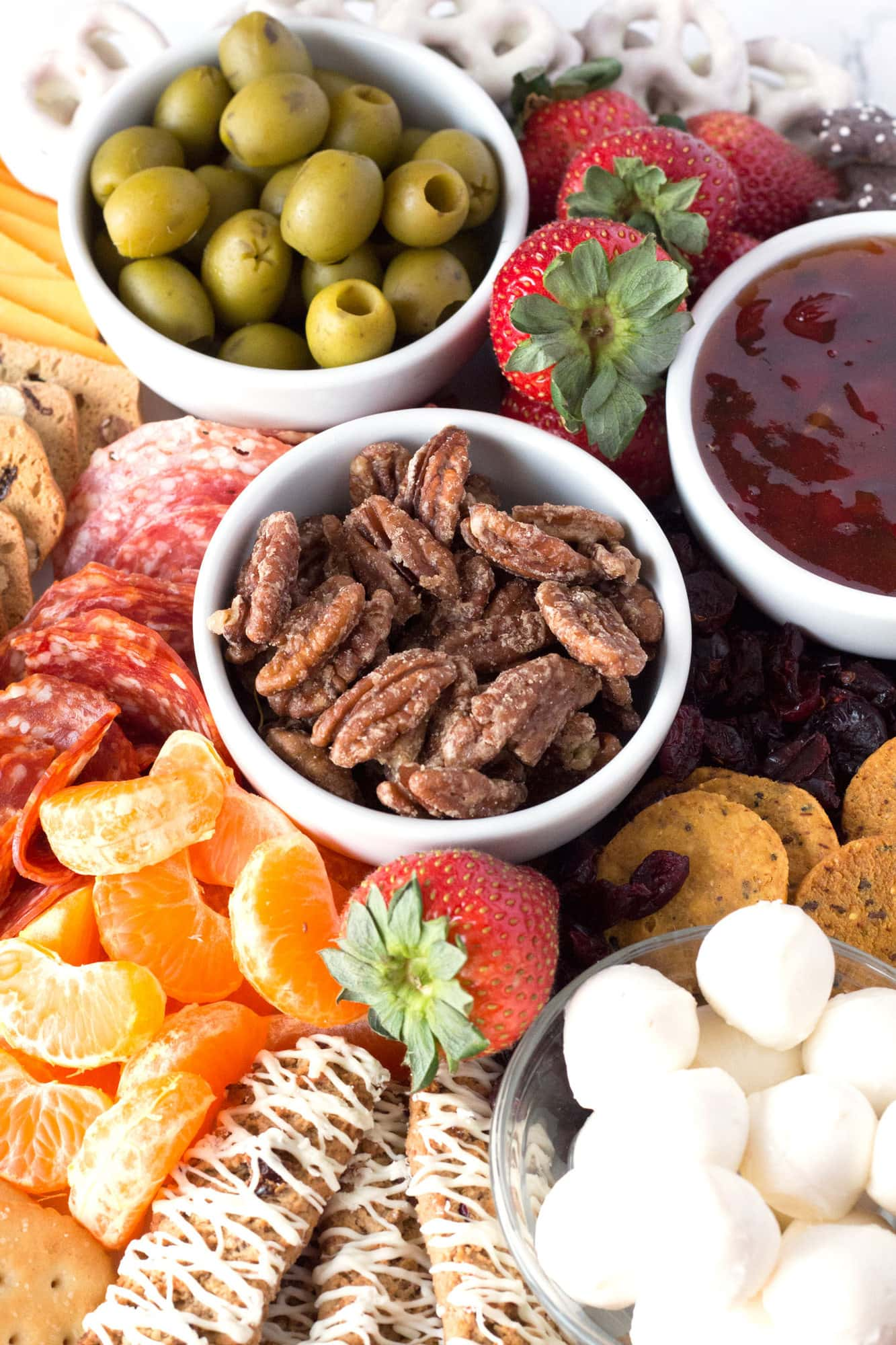 Sweet and salty Christmas snack board with oranges, cheese, cookies, olives, nuts, and other snack ideas.